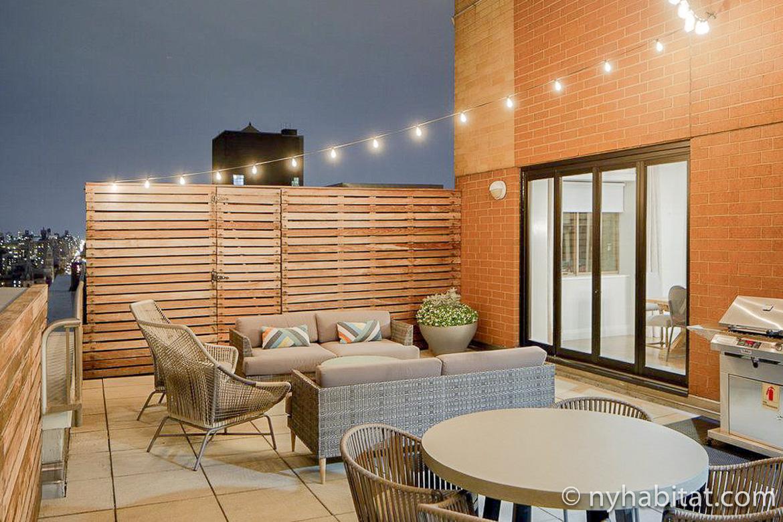 Photographie de l'espace détente du toit-terrasse de l'appartement NY-17339 avec son mobilier d'extérieur et ses guirlandes de lumières