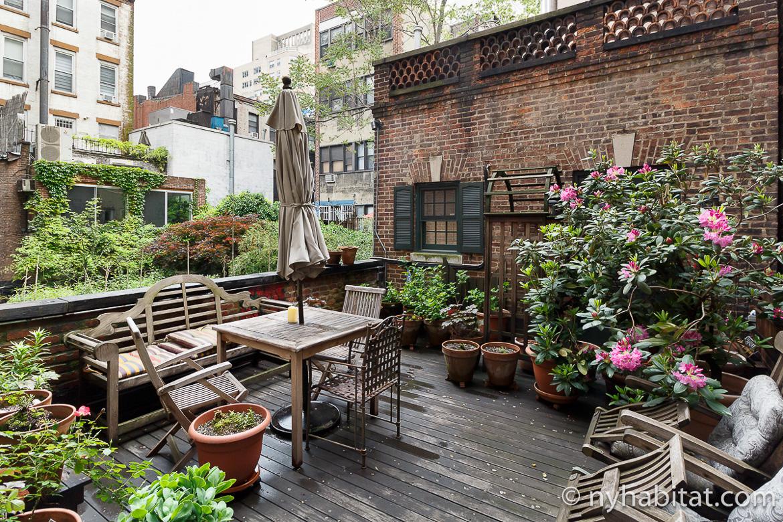 Photographie de la terrasse privative de l'appartement NY-17536 avec son mobilier d'extérieur et ses plantes en pots