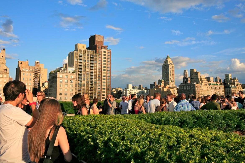 Photographie de personnes entourées de haies parfaitement taillées sur le toit-terrasse du Metropolitan Museum of Art