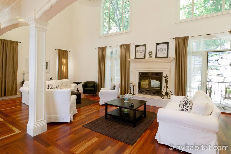 Photographie d'un petit salon dans la villa NY-15040 avec sa cheminée, ses baies vitrées et ses sièges blancs.