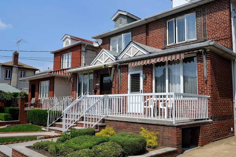 Photographie de maisons en briques de 2 étages dans un quartier du borough du Queens à New York.