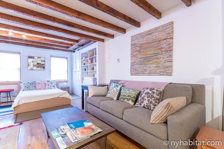 Photographie de la salle de séjour du studio NY-10856 avec son lit, son canapé et ses œuvres d'art