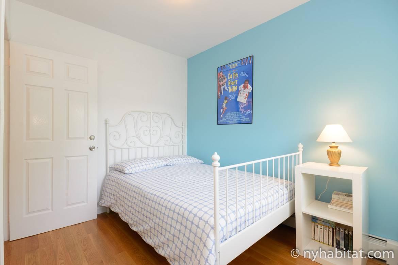 Photographie de chambre à coucher dans l'appartement NY-16234 avec son lit double, son placard et son mur bleu.