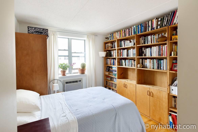 Photographie de la chambre à coucher dans l'appartement NY-16265 avec ses étagères et son lit double