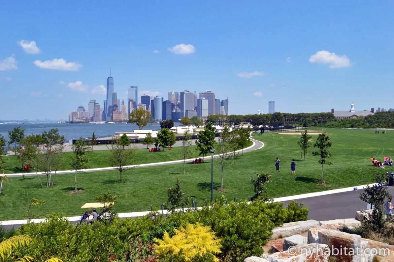 Photo de pelouses et de sentiers sur Governor's Island avec les gratte-ciel de Manhattan en fond.