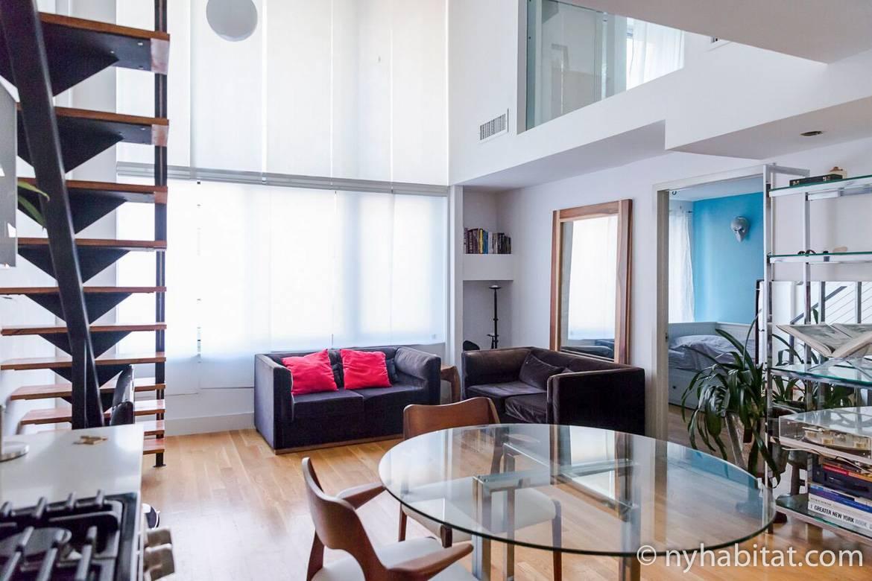 Photo du salon du NY-15911 avec canapé, table, chaises et escalier.