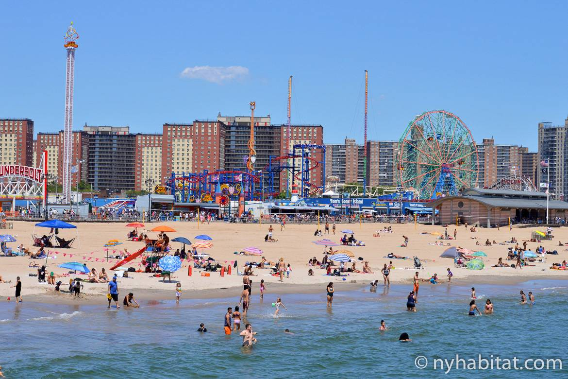 Photo de la plage de Coney Island, de baigneurs et du parc d'attraction en fond.