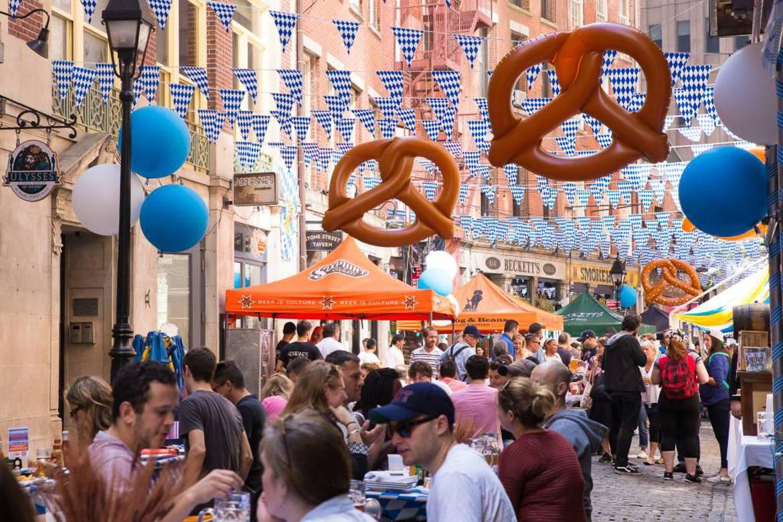 Photo de la célébration en plein air de l'Oktoberfest à New York, avec drapeaux bavarois et bretzels gonflables.