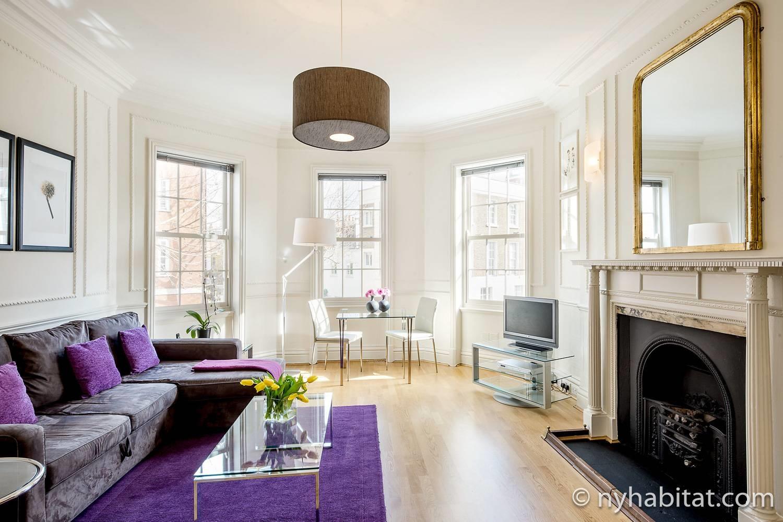 Photo du salon de l'appartement LN-319 avec une cheminée décorative, une table, des chaises et un canapé d'angle.