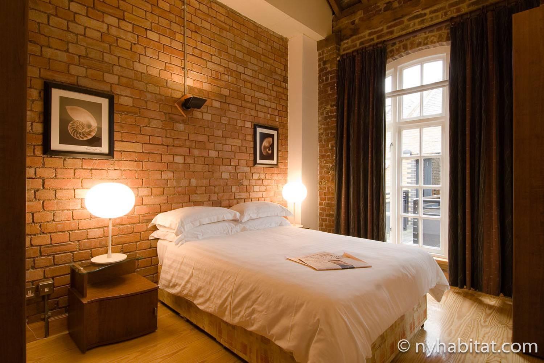 Photo de la chambre de l'appartement LN-692 avec des murs en brique apparente et un lit double.