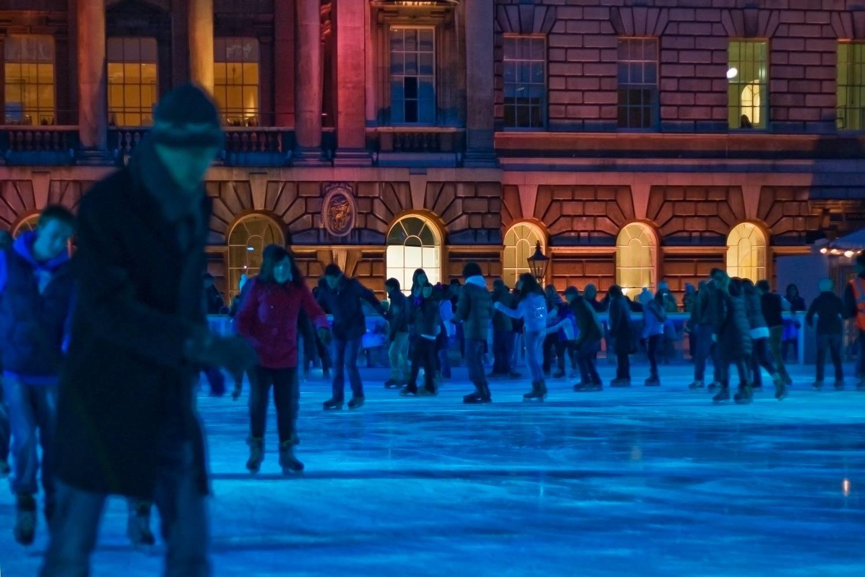 Photo de personnes faisant du patin à glace sur la patinoire de la Somerset House à Londres durant la nuit.