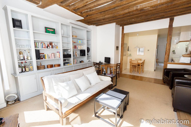 Photo du salon de l'appartement PA-3155 avec un canapé blanc et des étagères.