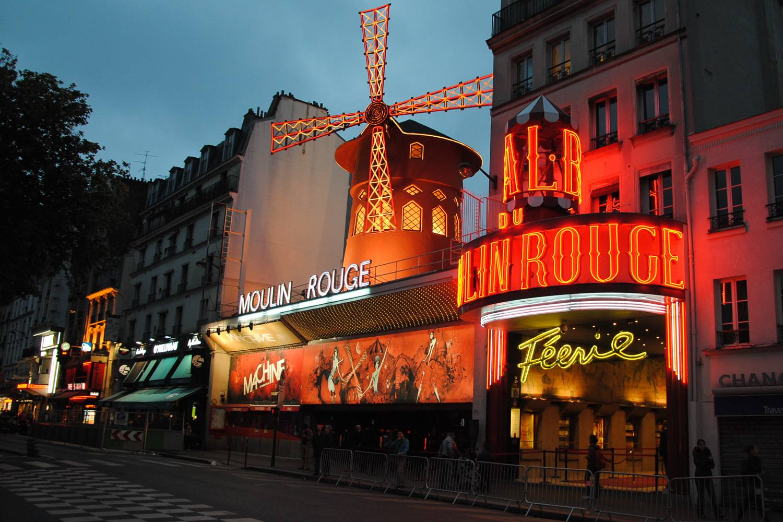 Photo du cabaret le Moulin Rouge à Paris, éclairé par des enseignes lumineuses à la nuit tombée.