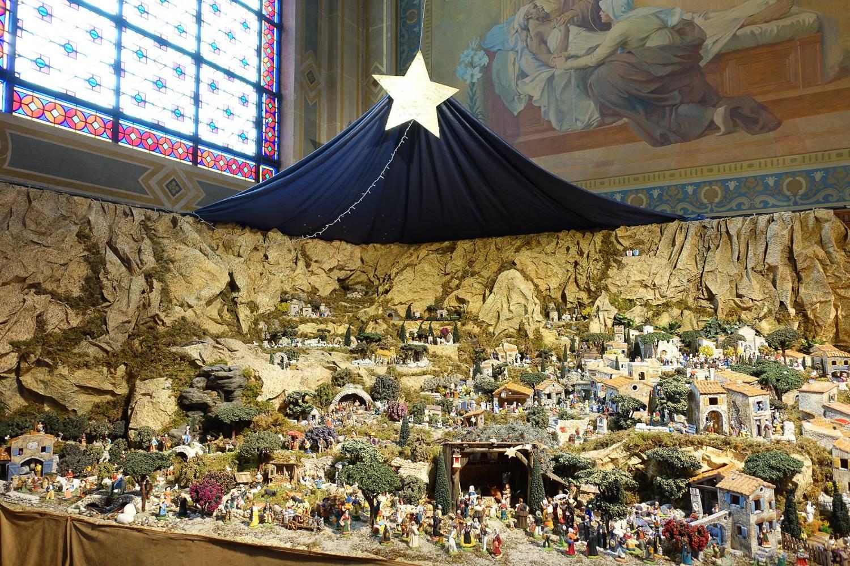Photo d'une crèche de la Nativité traditionnelle dans une cathédrale parisienne.