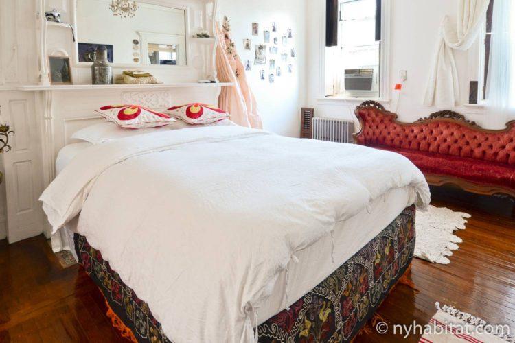 Photo d'un lit double et d'une causeuse dans la chambre de l'appartement NY-14848.