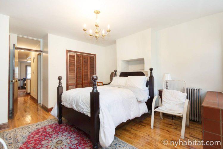 Photo d'un lit double, d'une chaise et d'un placard dans la chambre de l'appartement NY-17129.