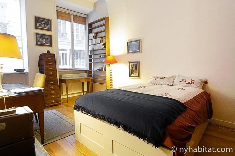 Photo d'une chambre de l'appartement PA-4187 avec lit double, bureau et étagères.
