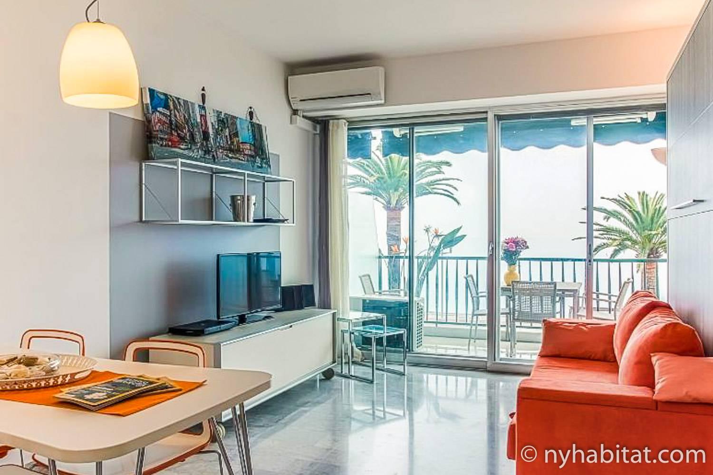 Photo du salon du PR-1217 avec télévision, canapé et porte-fenêtre menant au balcon.