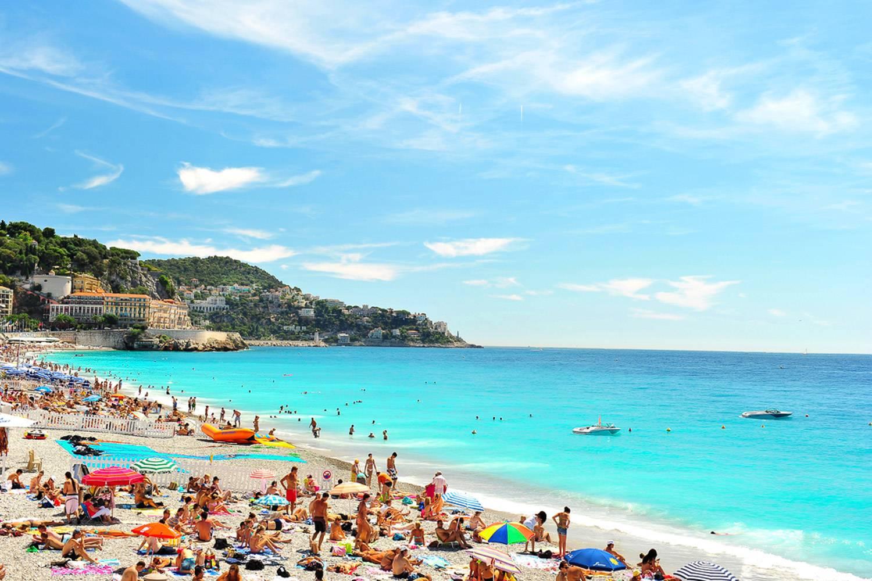 Photo de baigneurs sur le sable et de bateaux à proximité du rivage d'une plage à Nice.