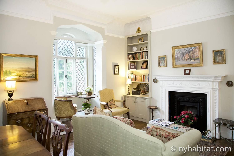 Photo du salon de l'appartement LN-1666 avec cheminée décorative, bureau, canapé et chaises.