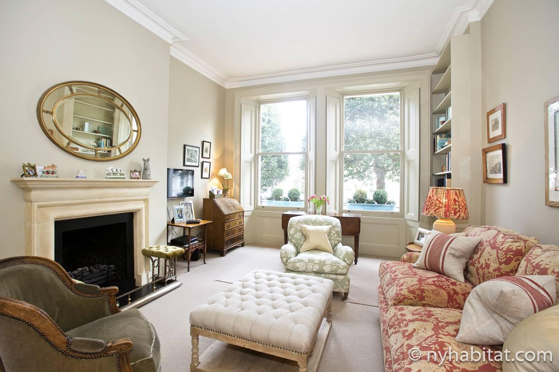 Photo du salon de l'appartement LN-1956 avec fauteuils, cheminée décorative et canapé.