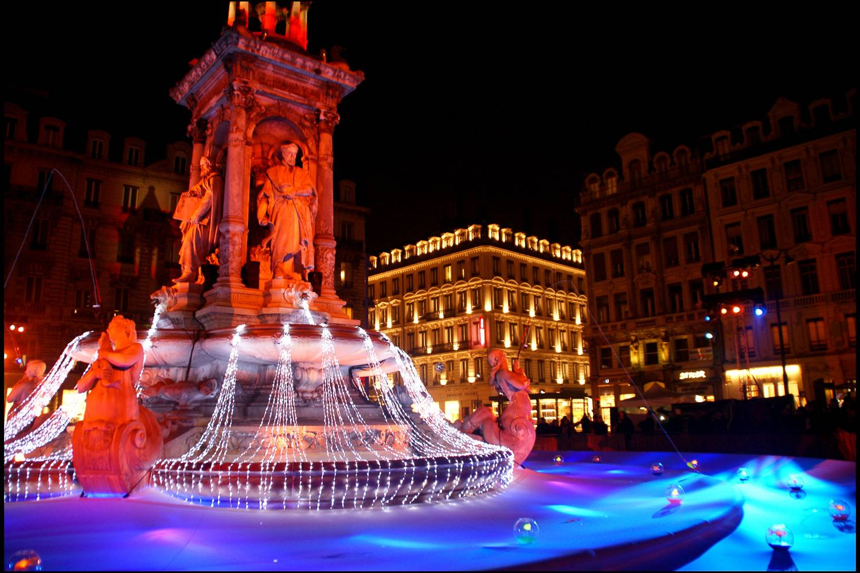 Photo d'une fontaine à Lyon décorée avec des illuminations pour la Fête des Lumières.