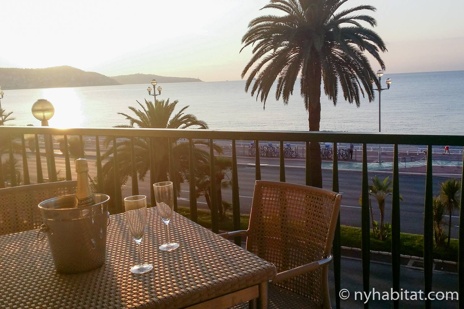 Photo du balcon privatif de l'appartement PR-1217 avec table, chaises, palmiers et vue sur la plage de Nice.