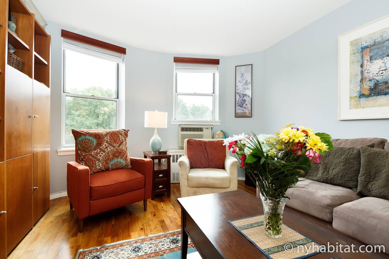 Photo du salon de l'appartement NY-14853 avec canapé, fauteuils, étagères et piano à queue.