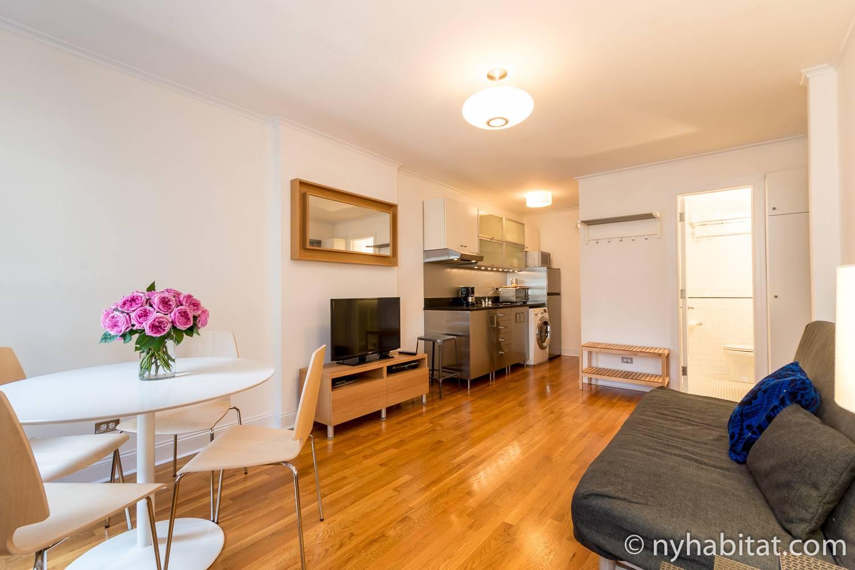 Photo de la pièce de vie de l'appartement NY-5193 avec canapé, télévision, table, chaises et cuisine.