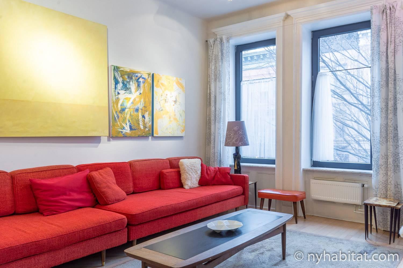 Photo du séjour de l'appartement NY-12274 offrant un grand canapé rouge, des œuvres d'art et une table basse.