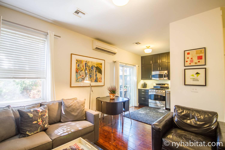 Photo du séjour et de la cuisine de l'appartement NY-15411 comprenant un fauteuil en cuir, un canapé, une petite table à manger et un poêle.