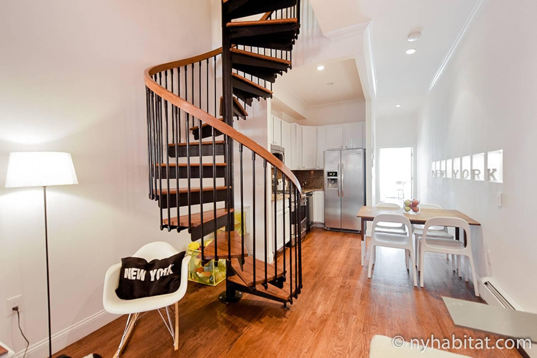 Photo du séjour et de la cuisine de l'appartement NY-15593 proposant un escalier en colimaçon, une table à manger et des chaises et un réfrigérateur.