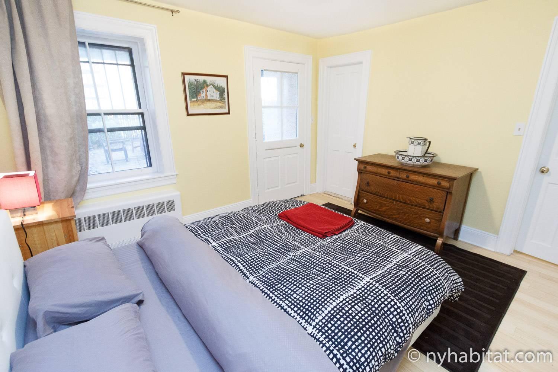 Photo de la chambre de l'appartement NY-16328 dotée d'un lit queen-size, d'une table de chevet et de fenêtres.