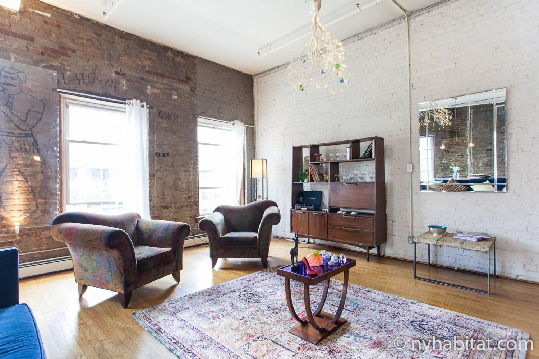 Photo du salon du NY-16930 avec fauteuils, miroir, bibliothèque et lustre.