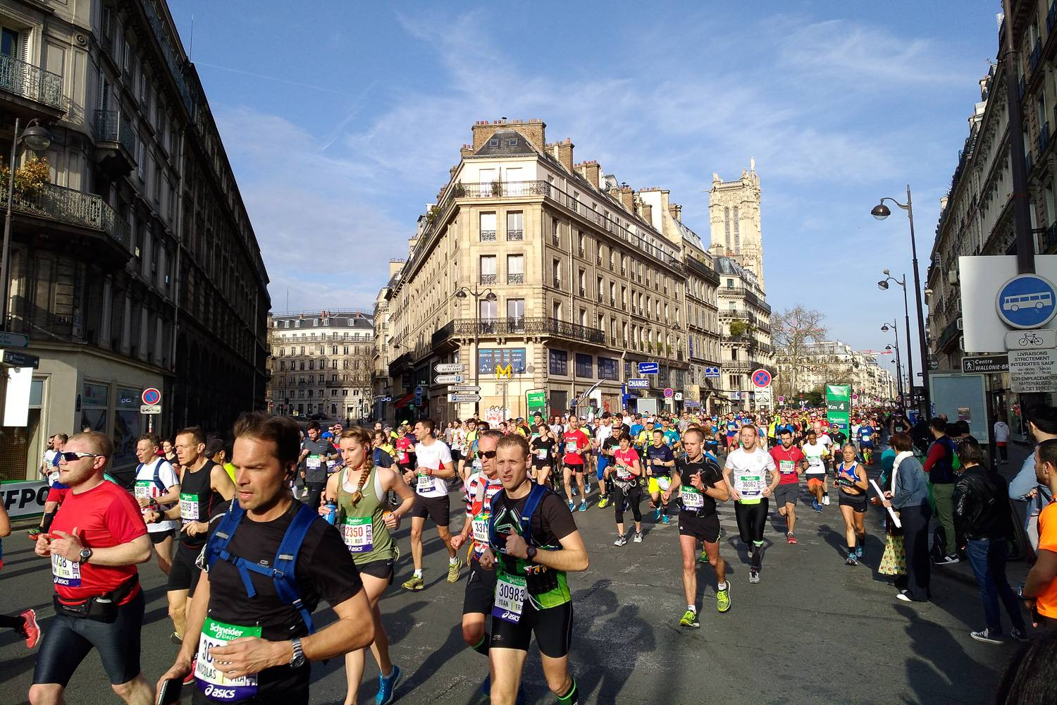 Photo de coureurs passant devant un immeuble haussmannien lors du marathon de Paris 2018.