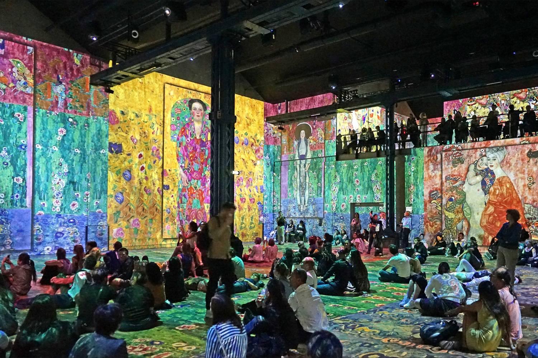 Photo de visiteurs assis au cœur de l'exposition numérique des œuvres de Gustav Klimt à l'Atelier des Lumières.