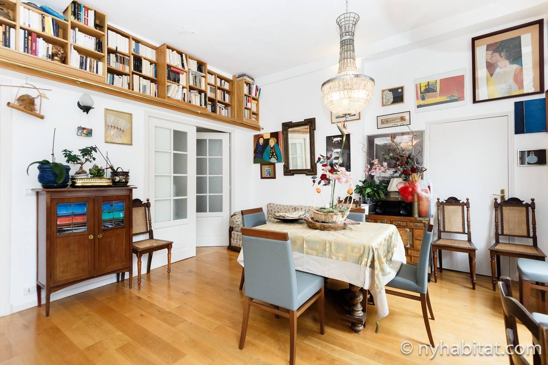 Photo de la pièce de vie de l'appartement PA-1460 avec table, chaises, lustre et étagères.