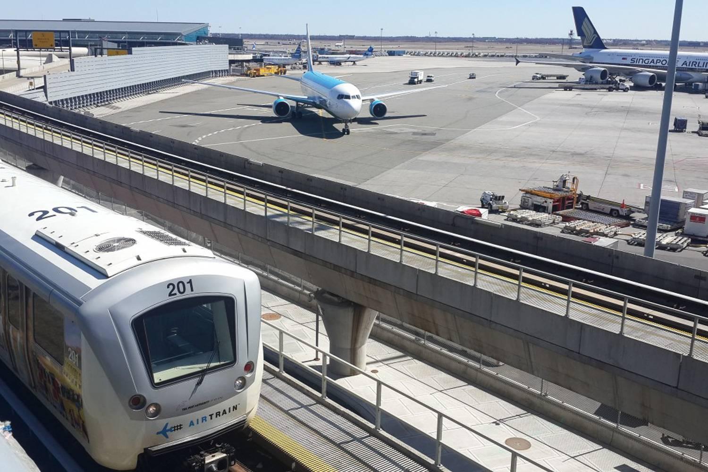 Photo de l'AirTrain de JFK voyageant entre les terminaux avec des avions sur le tarmac en arrière-plan.