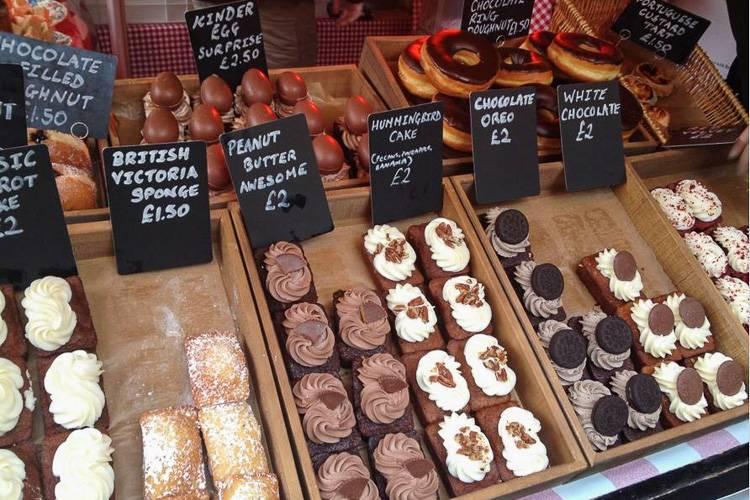 Photo de desserts et pâtisseries exposés sur un stand de boulangerie à Londres.