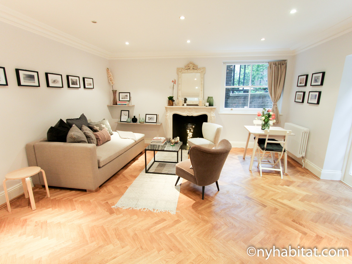 Photo de la pièce à vivre de l'appartement LN-1695 contenant un canapé, des fauteuils et une cheminée décorative.