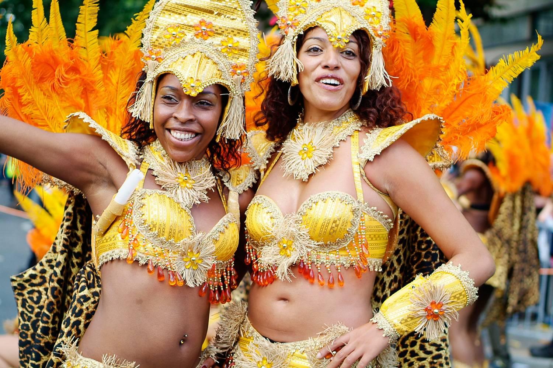 Photo de deux femmes en costumes jaunes sophistiqués, dansant au carnaval de Notting Hill.