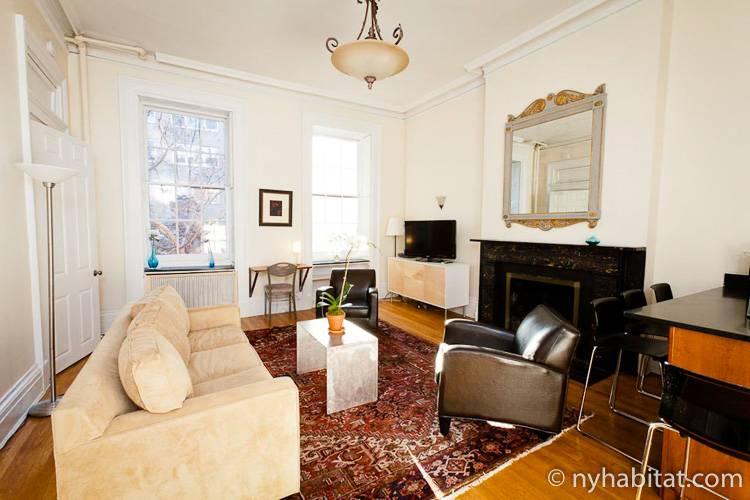 Photo de la pièce à vivre de l'appartement NY-15085 et de ses fauteuils, son canapé et sa cheminée décorative.