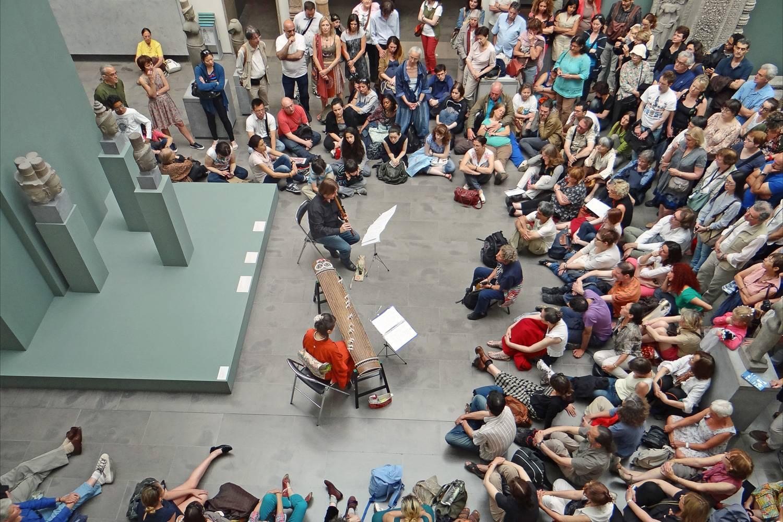 Photo d'un groupe de spectateurs admirant un duo au musée Guimet lors de la fête de la musique.