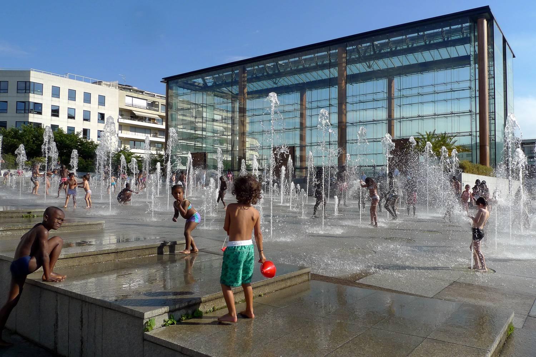 Photo d'enfants jouant dans les fontaines du parc André Citroën, à Paris.