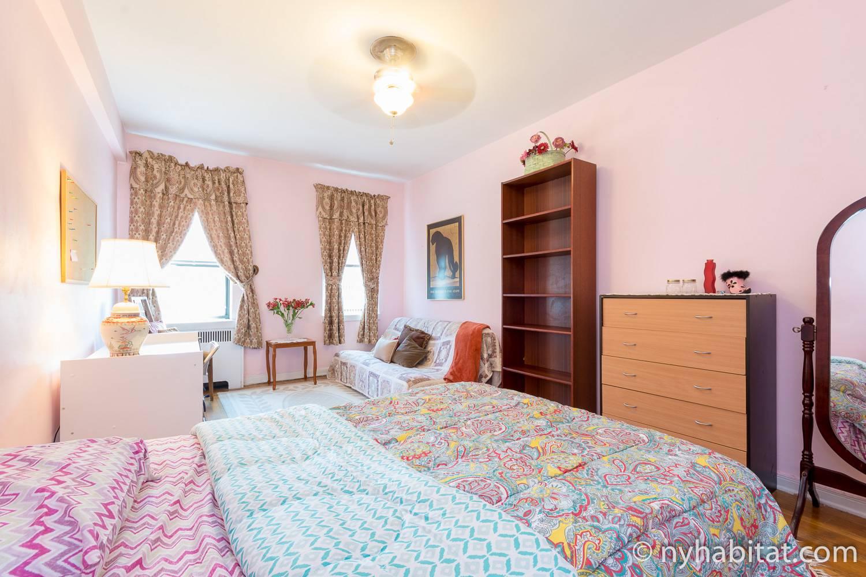 Photo de la chambre de l'appartement NY-6328, qui comprend un lit double, une commode et un canapé.