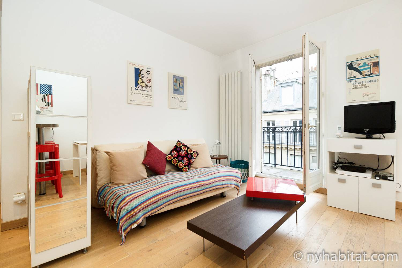 Photo de la pièce à vivre de l'appartement PA-3311 avec un canapé et une porte donnant sur le balcon.