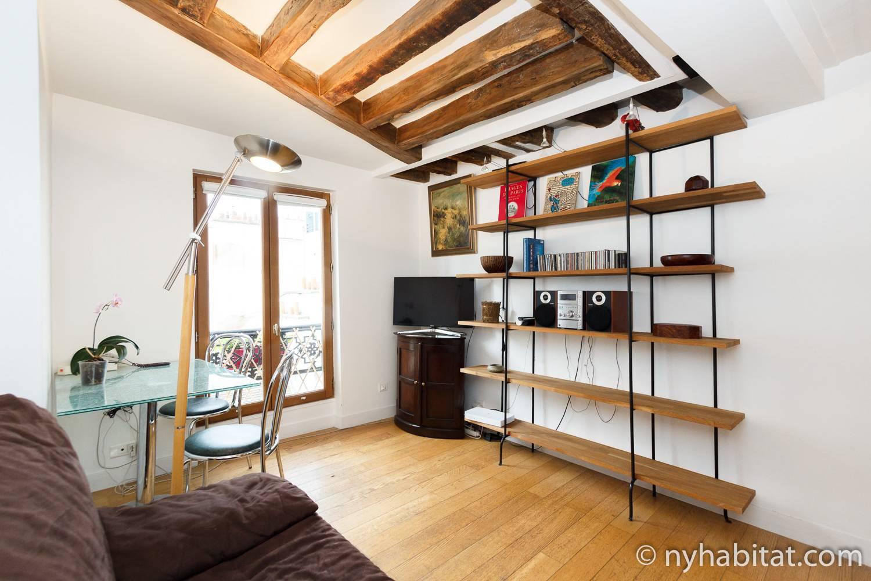 Photo de la salle à manger de l'appartement PA-3675 avec canapé, table et chaises, et bibliothèque.