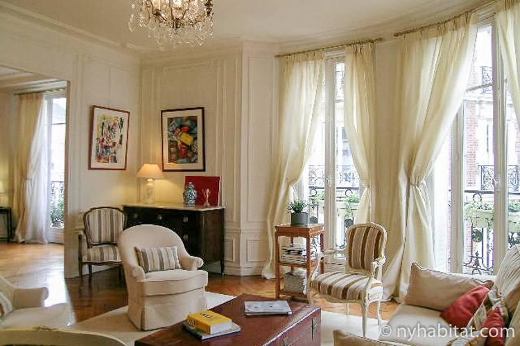 Photo de la pièce à vivre de l'appartement PA-3703 avec portes-fenêtres, canapé, et fauteuils.