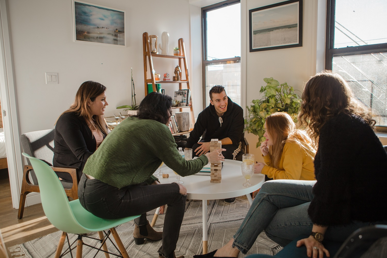 Photo de colocataires se retrouvant ensemble autour d'un jeu dans un appartement en co-living.