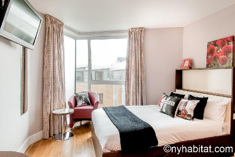 Photographie du salon de l'appartement LN-1170 avec un lit queen-size, une télévision et un fauteuil.